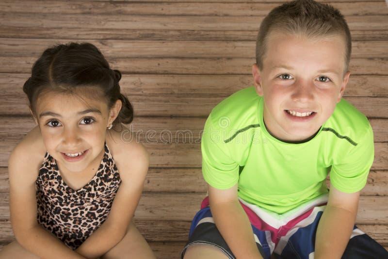 Gulligt pojke- och flickasammanträde på det wood golvet som ser upp royaltyfria bilder