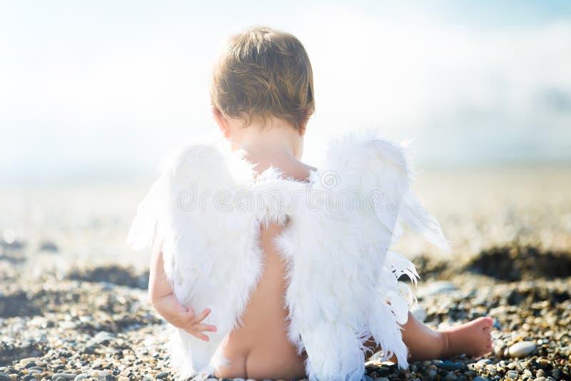 Gulligt pojkesammanträde på stranden royaltyfria bilder