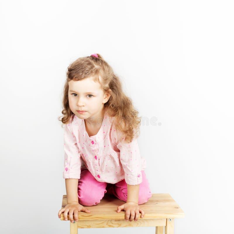 Gulligt sammanträde för litet barn på stolen och le bärande rosa färger fotografering för bildbyråer