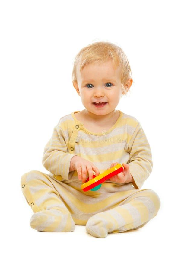 Gulligt sitta barnvakt på golv och leka med rattle arkivfoto