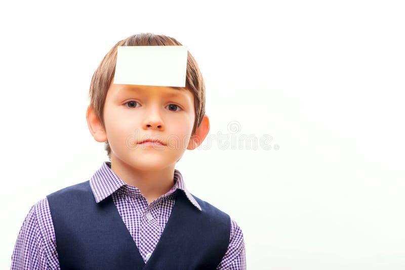 Gulligt skolbarn i dräkt med ett ark av papper på arkivfoto
