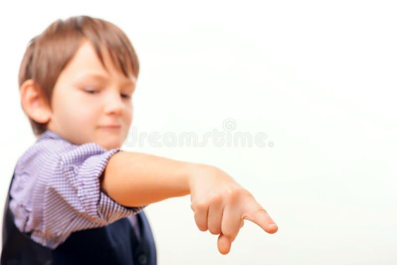 Gulligt skolbarn i dräkt som ner pekar royaltyfri fotografi