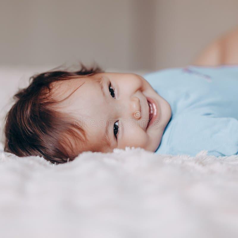 Gulligt skratta en årig flicka som ligger på säng och ser kamerahandlag hennes fot royaltyfria foton
