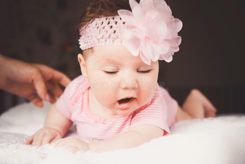 Gulligt sova som är härligt, och att gäspa behandla som ett barn flickan i rosa färger som ner hemma ligger på en vit säng Spädba royaltyfria foton