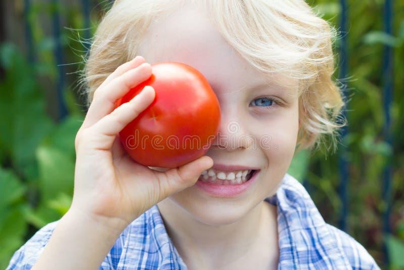Gulligt sunt barn som rymmer en organisk tomat över hans öga arkivfoto