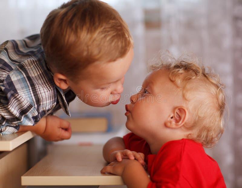 Gulligt syskon. Två lilla bröder är kyssande. arkivbild