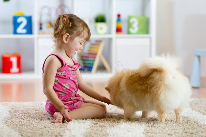 Gulligt ungeflickasammanträde på golvet med hennes hund royaltyfri foto