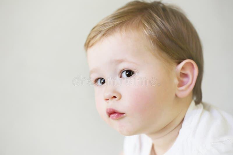 Gulligt ungt barn med allvarligt uttryck arkivbild