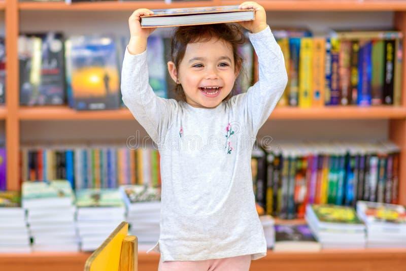 Gulligt ungt litet barn som står och rymmer boken i huvud Barnet i ett arkiv, shoppar, bokhandeln royaltyfria foton