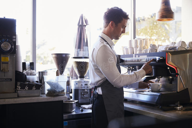 Guloseimas de Barista Making Coffee In usando a máquina fotos de stock