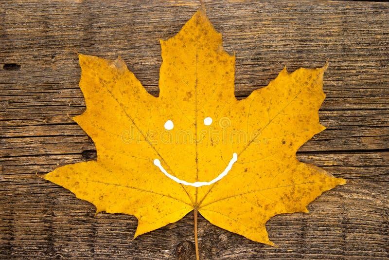 Gult blad för höst med leende på lantlig träbakgrund autum royaltyfri fotografi