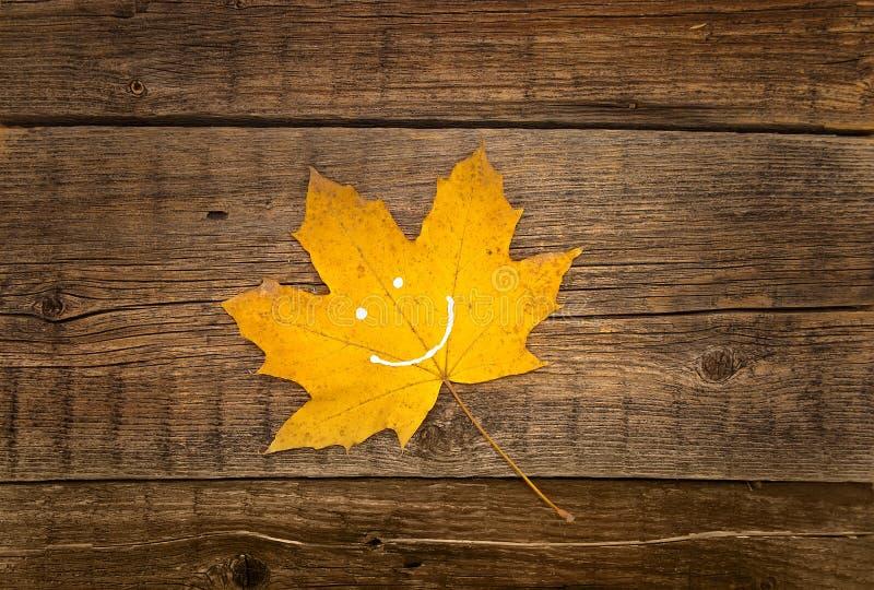 Gult blad för höst med leende på lantlig träbakgrund autum royaltyfria bilder