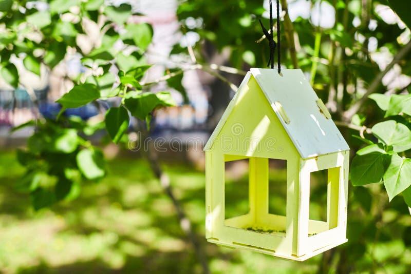 Gult fågelhus som hänger från trädet och omger av frodig lövverk arkivfoto