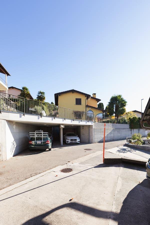 Gult hus med parkering som fördjupas i den schweiziska monteringen arkivfoto