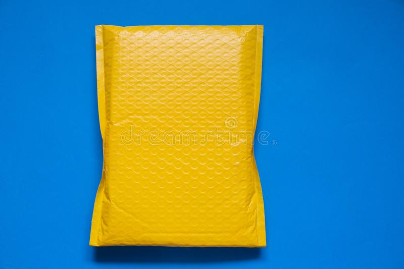 Gult kuvert som göras av bubblasjalen för att förhindra något från att knuffa till eller stötsäkert på blå bakgrund arkivbild