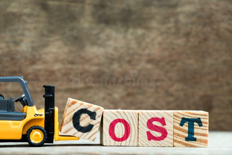 Gult kvarter C för bokstav för leksakgaffeltruckhåll som avslutar ordkostnad på träbakgrund arkivfoto