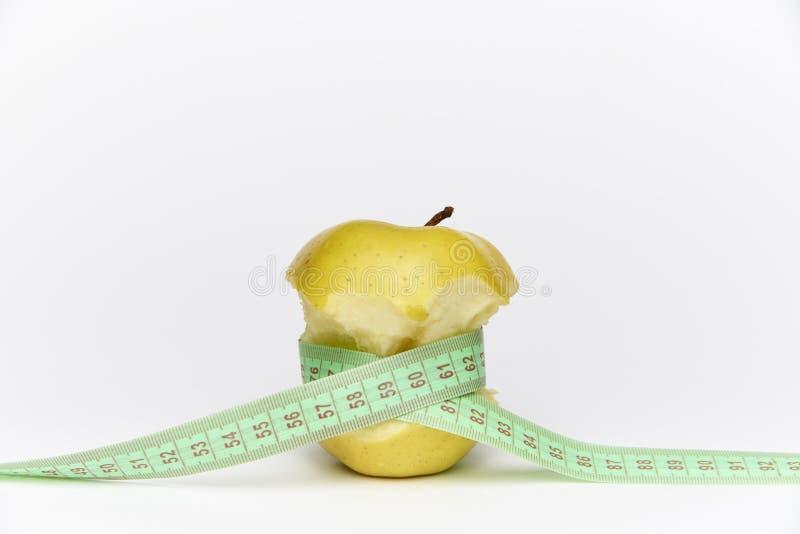 Gult moget bitit äpple med en mete royaltyfria bilder
