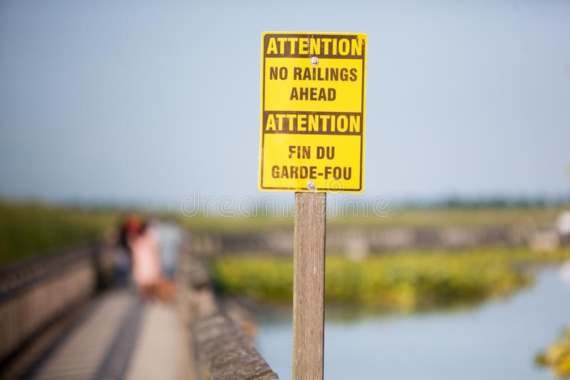 Gult och brunt strandpromenadtecken som varnar ingen räcke framåt arkivbild