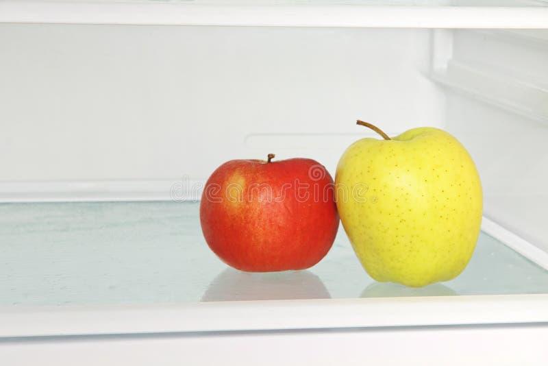 Gult och rött äpple i inhemskt kylskåp arkivfoton