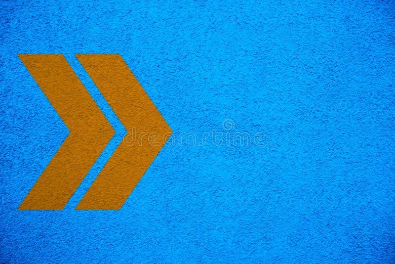 Gult orange piltecken som pekar rätt riktning över bakgrund för vägg för intensiv ljus blå färgstuckatur grov royaltyfria bilder