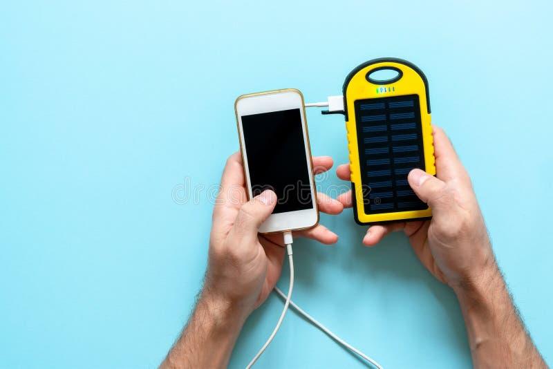 Gult solenergibatteri av en apparat på en blå bakgrund i händerna av en man royaltyfri fotografi