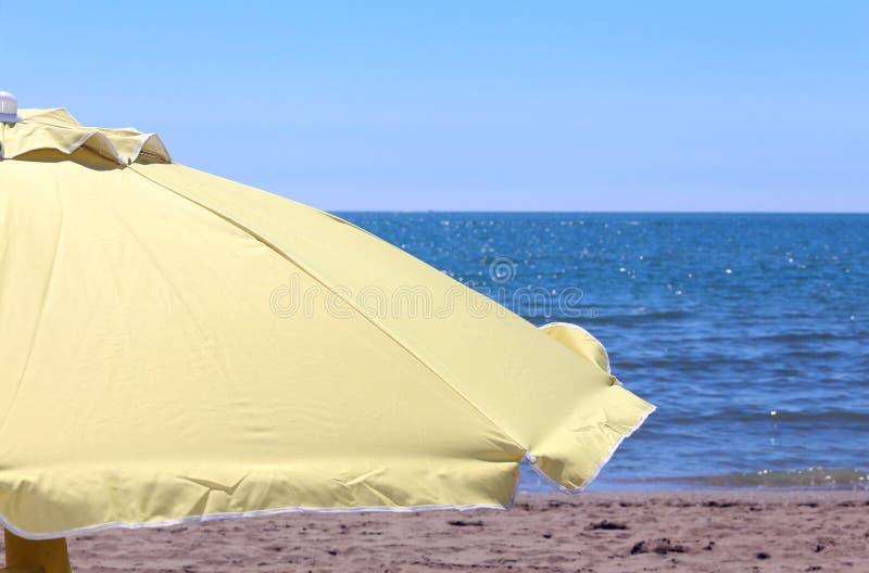 gult solparaply på kusten av havet i den varma sommaren royaltyfri bild