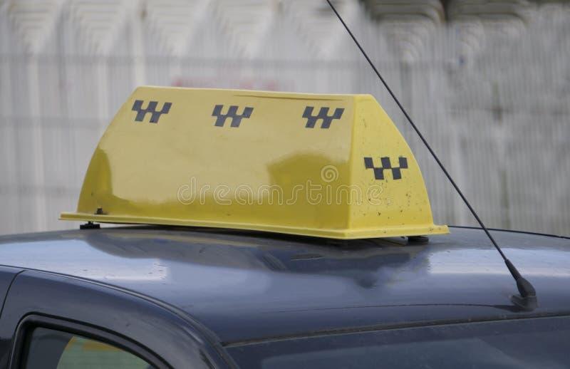 Gult taxitaktecken med telefonen, pengar och kreditkortar på, closeup arkivfoto