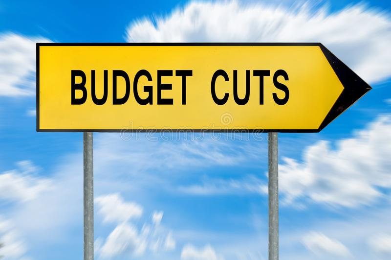 Gult tecken för gatabegreppsbudgetnedskärningar arkivfoton
