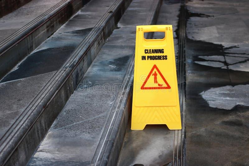 Gult tecken för varningslokalvårdframsteg på golvet utomhus royaltyfri fotografi