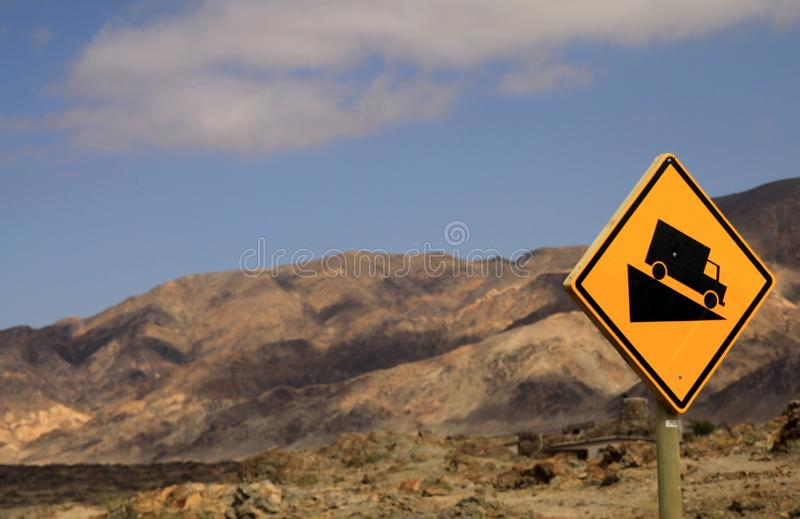 Gult tecken med den svarta lastbilen i torr ointressant miljövarning för brant lutning i den Atacama öknen, Chile royaltyfri fotografi