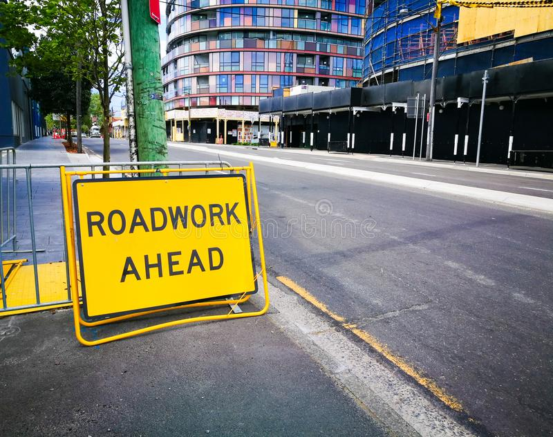 Gult trafiktecken för rektangel för vägarbete framåt på en trottoar arkivbilder