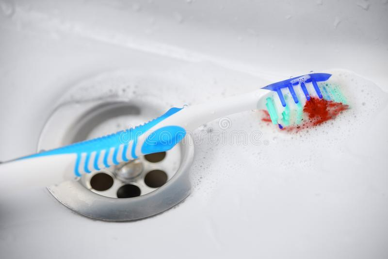 Gum disease concept. Blue toothbrush with toothpaste and blood near washbasin sink royalty free stock photo
