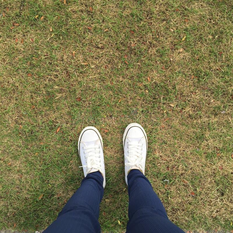Gummiüberschuhe auf städtischem Schmutzhintergrund Begriffsbild von Beinen stockfotos