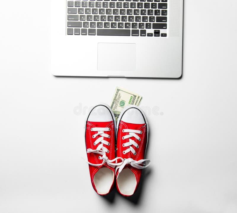 Gummiüberschuhe, Geld und Laptop lizenzfreie stockfotos
