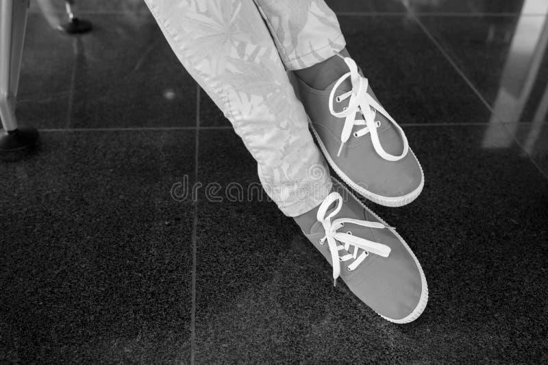 Gummiüberschuhe mit gelben Spitzeen auf weiblichen Beinen stockfotografie