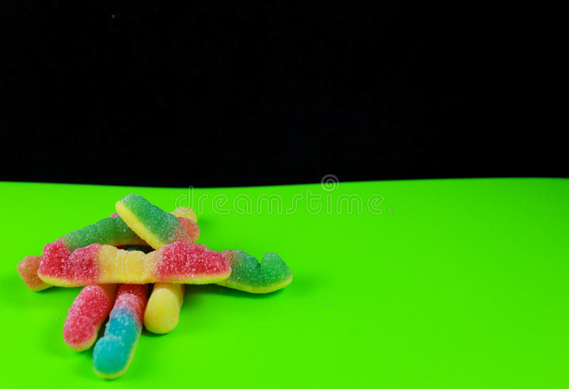 Gummi worms in a pop art style. Gummi candy in a pop art style on a green and black background royalty free stock image