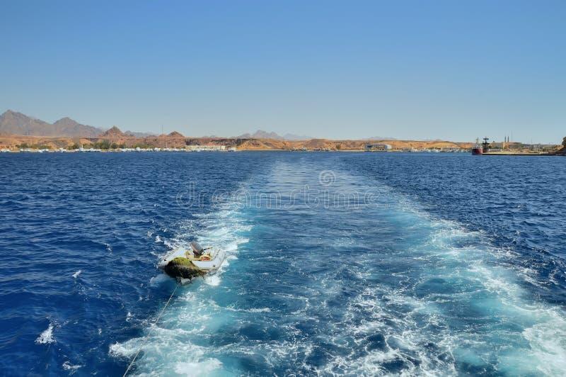 Gummiboot mit Außenbordmotor unmittelbar nach dem Schiff, auf dem Hintergrund im Hintergrund, in den Gebäuden, in den Bergen und  lizenzfreies stockfoto