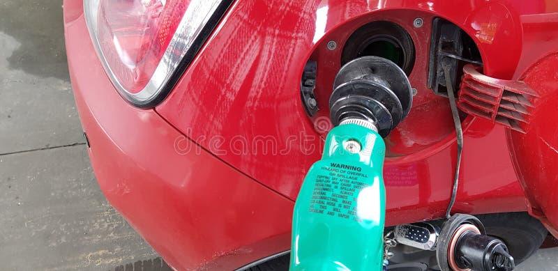 Gummibränsledysa inom gasbehållaren av mini- fyllande bensin för sportbil i självservicestation arkivbild