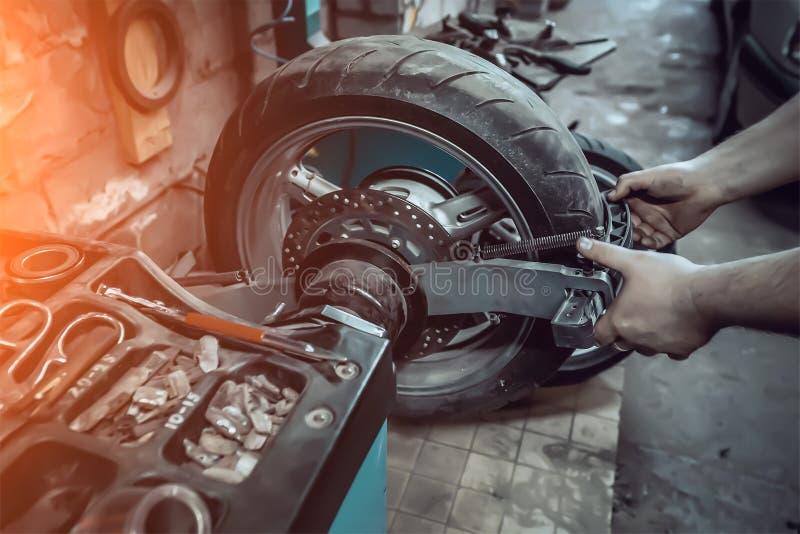 gummihjulservice av ett motorcykelhjul arkivbild