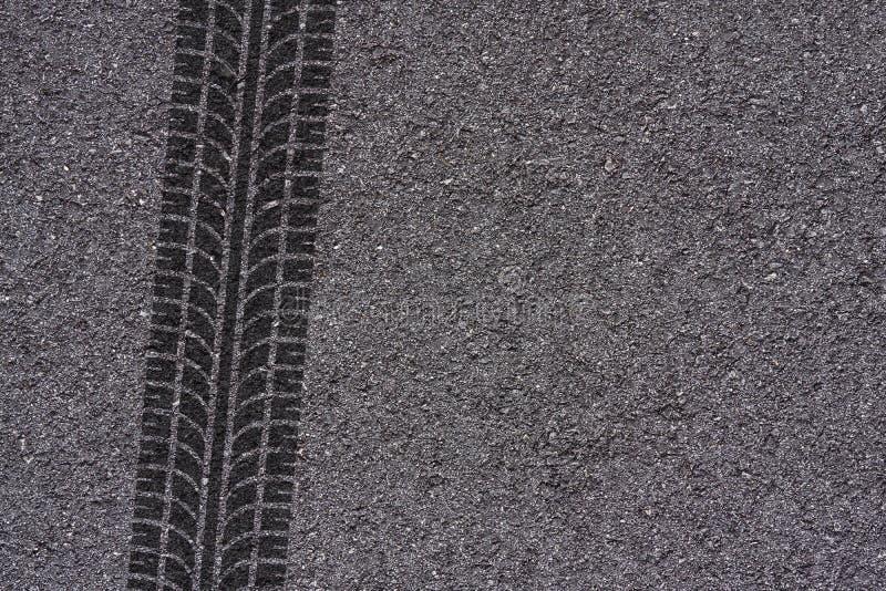 Gummihjulspår på asfalt arkivbilder
