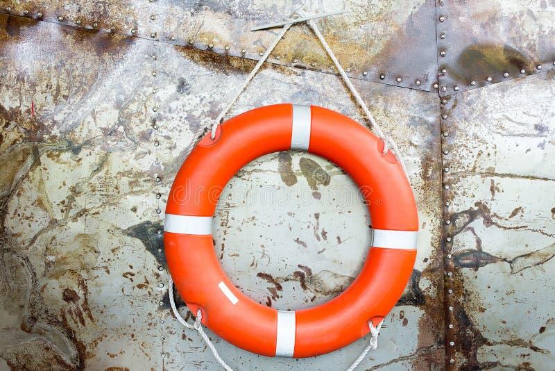 Gummiringfall auf der Stahlwand Orange Rettungsschwimmengummi Roter Rettungsgürtel auf Wand nahe dem Ozean Rettungsring oder Leib stockfoto