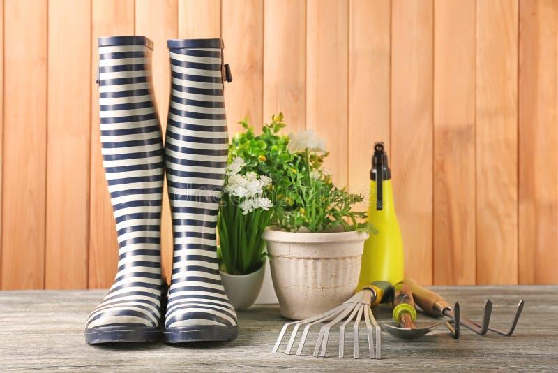 Gummistiefel, Blumentöpfe und Gartenarbeitwerkzeuge auf hölzernem Hintergrund lizenzfreie stockfotografie