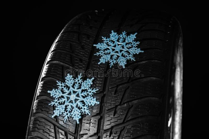 Gumowa zimy opona z płatkami śniegu na ciemnym tle zdjęcie stock