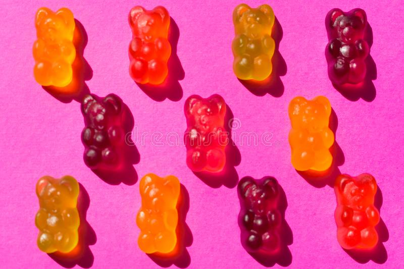 Gumowaci cukierek galarety niedźwiedzie na różowym tle, zdjęcie royalty free