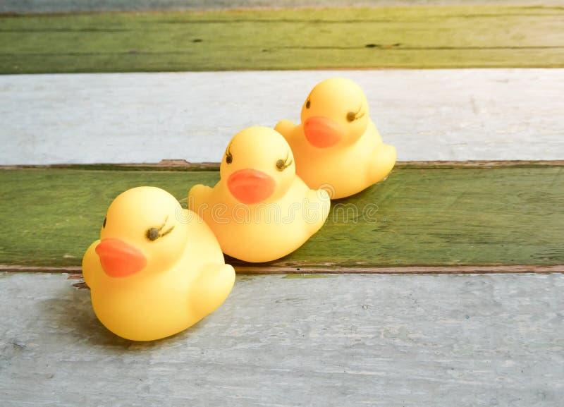 Gumowe żółte kaczki bawją się na drewnianym stołowym tle obrazy royalty free