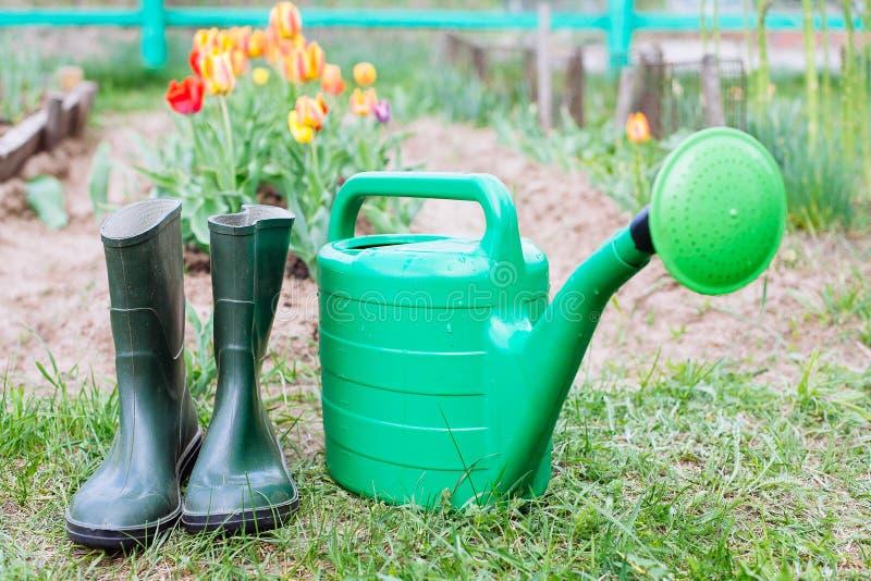Gumowi buty z podlewanie puszką na trawie fotografia stock