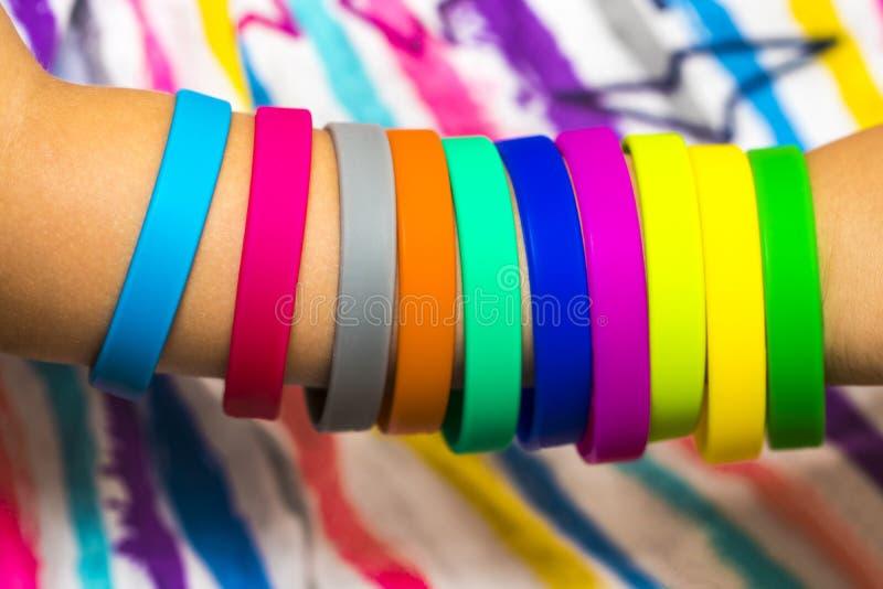 Gumowi zespoły na ręce Dziewczyny wręczają z bransoletkami robić gumowy b fotografia royalty free