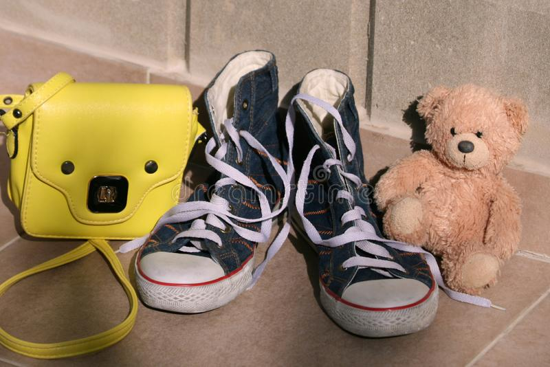 Gumshoes, handbag and teddy bear in front of stone wall royalty free stock photos