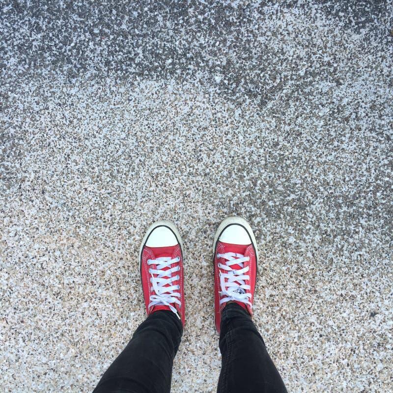 Gumshoes op stedelijke grungeachtergrond Beeld van benen in laarzen op stadsstraat Voeten schoenen die in openlucht lopen De jeug stock afbeeldingen