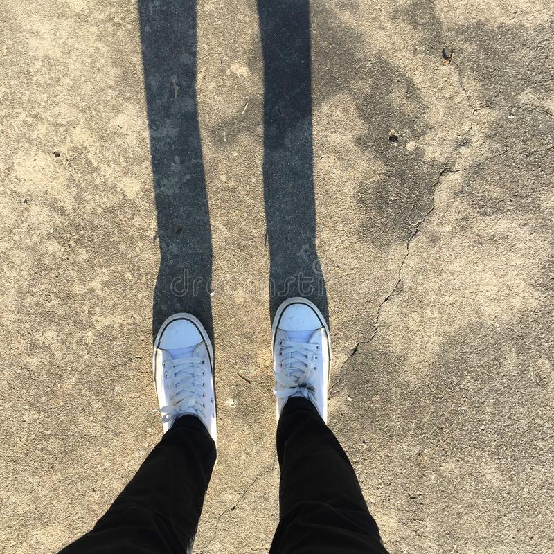 Gumshoes on urban grunge background of asphalt. Conceptual image of legs in boots on city. Feet shoes walking in outdoor. stock images